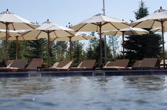 Piscine d'hôtel avec les canapés vides du soleil Photos libres de droits