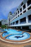 Piscine de dauphin, canapés du soleil à côté du jardin et bâtiments Image stock
