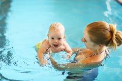 Piscine de enseignement de bébé de mère photographie stock