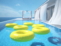 Piscine de luxe avec des swimmrings rendu 3d Images libres de droits