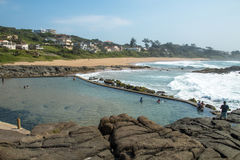 Piscine de marée contre la plage et les terrains à bâtir résidentiels côtiers Photos stock