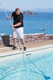 Piscine de nettoyage d'homme au-dessus de la mer Photos libres de droits