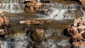 Piscine de roche avec de l'eau l'écoulement de l'eau au-dessus de la pierre rougeâtre photo stock