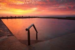 Piscine de roche d'océan sous le ciel rouge de flambage Photographie stock libre de droits