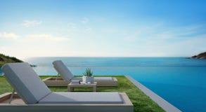 Piscine de vue de mer près de terrasse et lits dans la maison de plage de luxe moderne avec le fond de ciel bleu, chaises longues Image libre de droits