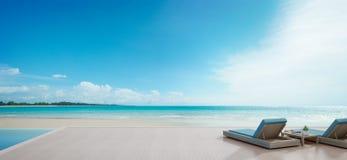 Piscine de vue de mer près de terrasse et lits dans la maison de plage de luxe moderne avec le fond de ciel bleu, chaises longues Photo stock