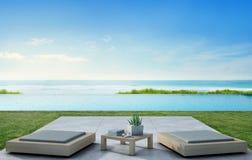 Piscine de vue de mer près de terrasse et meubles modernes dans la maison de plage de luxe avec le fond de ciel bleu Image libre de droits