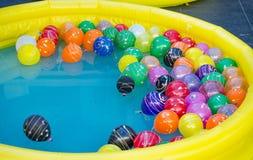 Piscine en caoutchouc jaune avec les boules colorées dans l'eau photographie stock