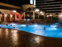 Piscine la nuit au bâtiment d'hôtel Images libres de droits