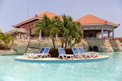 Piscine luxueuse avec des chaises longues et des palmiers, concept de luxe de vacances photo libre de droits
