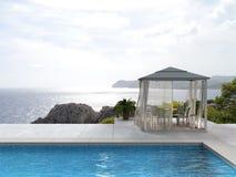 Piscine, pavillon et la mer Image stock
