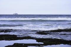 Piscines de roche sur le bord de mer avec l'horizon d'océan et la plate-forme de forage de pétrole dans la distance photo libre de droits