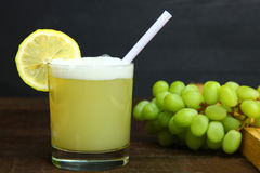 Pisco sour. Lemon and a bunch of grapes on a wooden table on black background royalty free stock photography