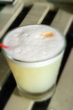 Pisco Sour. Peruvian cocktail named Pisco Sour made of Pisco (Peruvian grape schnaps),lime juice, syrup, egg white, and angostura (bitter fluid) drops on top ( Stock Photos