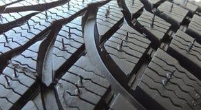 Pise a área do pneu de carro moderno novo com blocos e os reforços fecham-se acima Fotos de Stock Royalty Free
