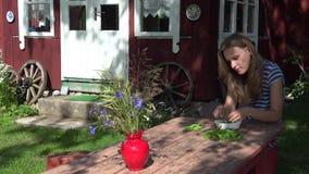 Piselli delle coperture della ragazza alla tavola di legno in paese con la vecchia casa 4K stock footage