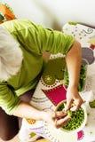 Piselli di pulizia della donna più anziana dai baccelli Fotografia Stock Libera da Diritti