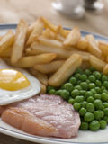 Piselli e patatine fritte dell'uovo fritto della bistecca del Gammon Fotografia Stock