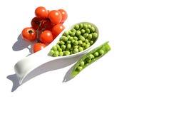 Piselli freschi con i pomodori Immagini Stock