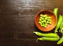 Piselli freschi verdi in piatto di legno Fotografia Stock