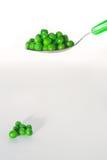 Piselli su un cucchiaio Immagini Stock Libere da Diritti