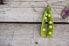 Pisello aperto di verde sulla tavola di legno Fotografia Stock