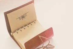 Piska anteckningsboken med pennbilden av ett flygplan ordna till för att tillfoga text eller modellen Arkivbild