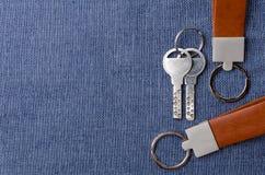 Piska den nyckel- kedjan med tangenter på blå tygbakgrund Royaltyfri Foto
