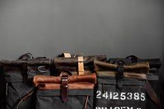 Piska handväskor nära den gråa väggen i rummet Arkivbilder