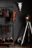 Piska handväskor och läderbälten nära väggen Royaltyfria Bilder