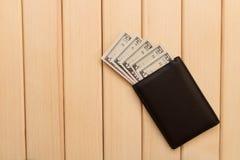 Piska plånboken, dollar och mynt på bakgrundsljuswooden fotografering för bildbyråer