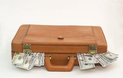 Piska portföljen med pengar som kommer ut ur sidorna royaltyfri bild