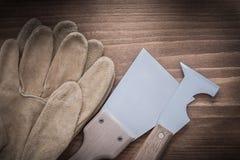 Piska säkerhetshandskar och glansiga konstruktionsspatlar på trä b Arkivfoton