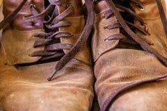 Piska skor, gammalt Sjaskig brun hud Sönderslitna skosnöre arkivbilder