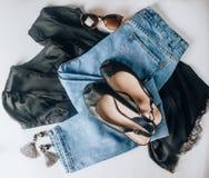 Piska svarta skor, jeans, svarta siden- t-skjortor, solglasögon och örhängen för begreppsframsida för skönhet blå ljus kvinna för fotografering för bildbyråer
