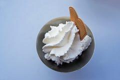 Piskad kräm och ett kex över knappt synlig glass i A M. Royaltyfri Fotografi