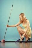 Piso arrebatador de la mujer elegante con la escoba Imagen de archivo libre de regalías