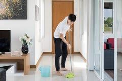 Piso asiático de la limpieza del hombre joven en casa Foto de archivo libre de regalías