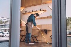 Piso de la limpieza del trabajador con barrido Fotografía de archivo libre de regalías