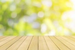 Piso de madera con el bokeh verde colorido de la naturaleza Foto de archivo