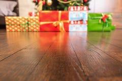 Piso de madera con los regalos del Año Nuevo en el fondo Fotos de archivo