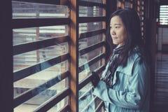 Piso de madera del ion derecho asiático de la mujer en castillo japonés y mirada al exterior fotos de archivo