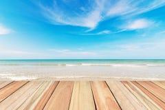 Piso de madera en fondo de la playa y del cielo azul