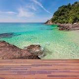 Piso de madera en la playa con las rocas y el mar de la turquesa, beautifu Fotografía de archivo