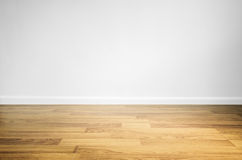 Piso de madera laminado con la pared blanca imágenes de archivo libres de regalías