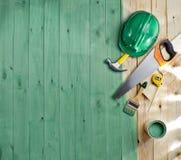Piso de madera verde con un cepillo, una pintura, herramientas y un casco Foto de archivo