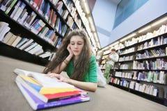 Piso de Studying On Library del estudiante Fotografía de archivo libre de regalías