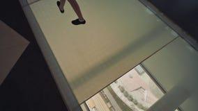 Piso electrónico y transparente de cristal, que está sobre la mucha altitud El capítulo de Dubai es uno de la última señal de metrajes