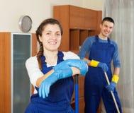 Piso feliz de la limpieza del equipo de los limpiadores Imágenes de archivo libres de regalías