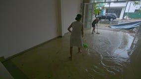 Piso inundado limpio del sitio del hombre de la mujer después del tifón devastador